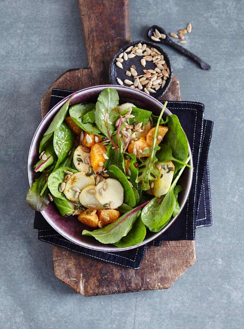 A mixed leaf salad with Jerusalem artichokes, tangerines, and sunflower seeds - 'Tip Top Topinambur'