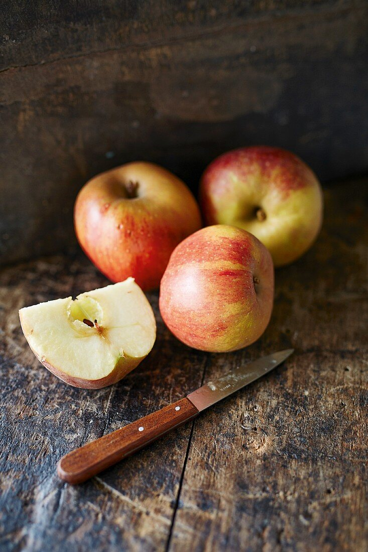 Whole and sliced Boskop apples with a knife on a wooden background