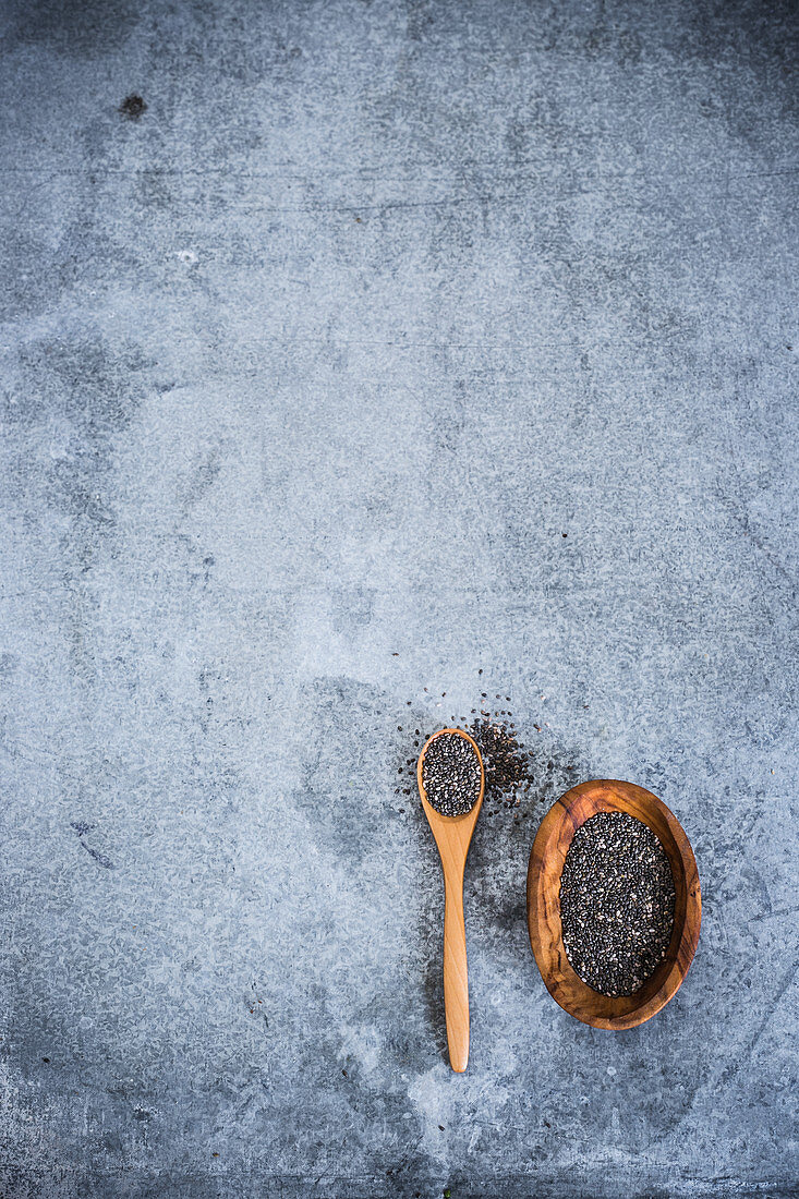 Black chia seeds on a wooden spoon and in a wooden bowl