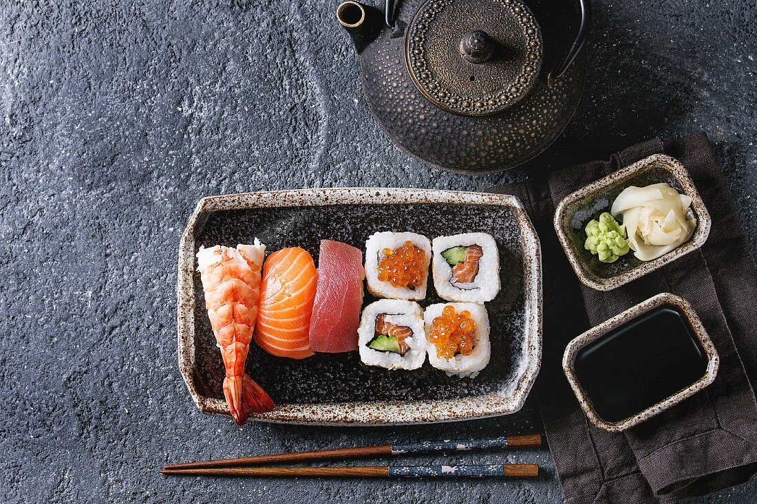 Nigiri and maki sushi rolls on a ceramic plate with soy sauce, wasabi and ginger
