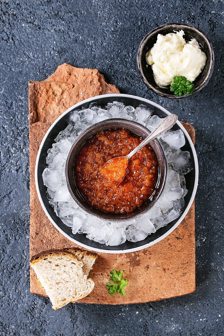 Bowl of red caviar on ice with spoon served with sliced bread, butter and herbs on terracotta board