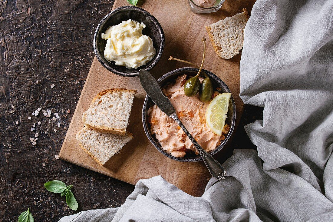 Black bowl of salmon pate with red caviar served with butter, sliced bread, capers, vintage knife and herbs