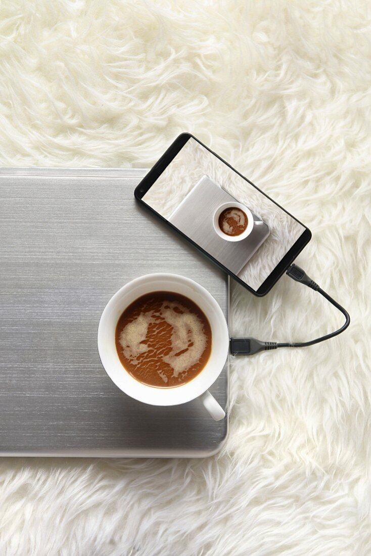 A cup of coffee and a cell phone connected to laptop, image displayed on smartphone