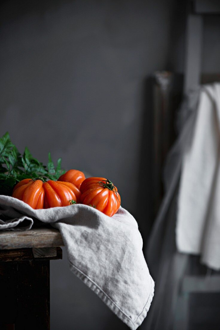 Beefsteak tomatoes on a cloth and kitchen table in a country house kitchen