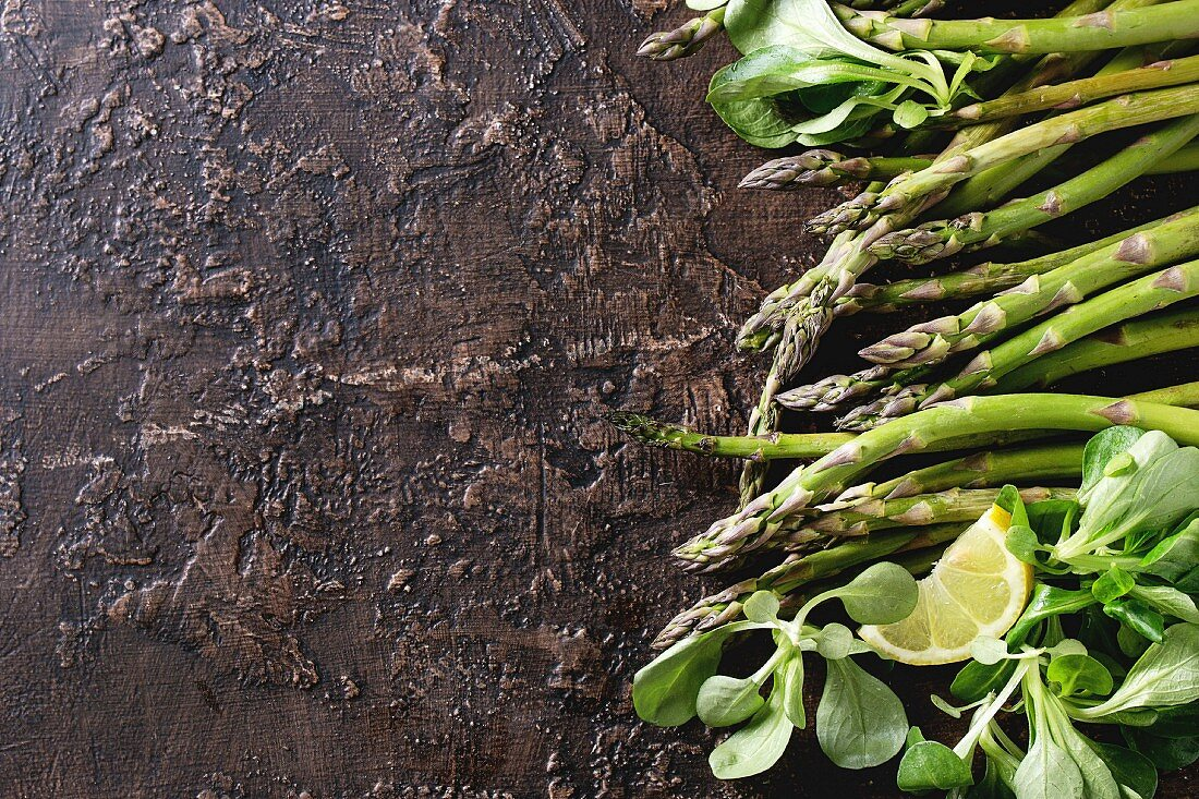 Green asparagus with green lettuce leaves and sliced lemon on a vintage background