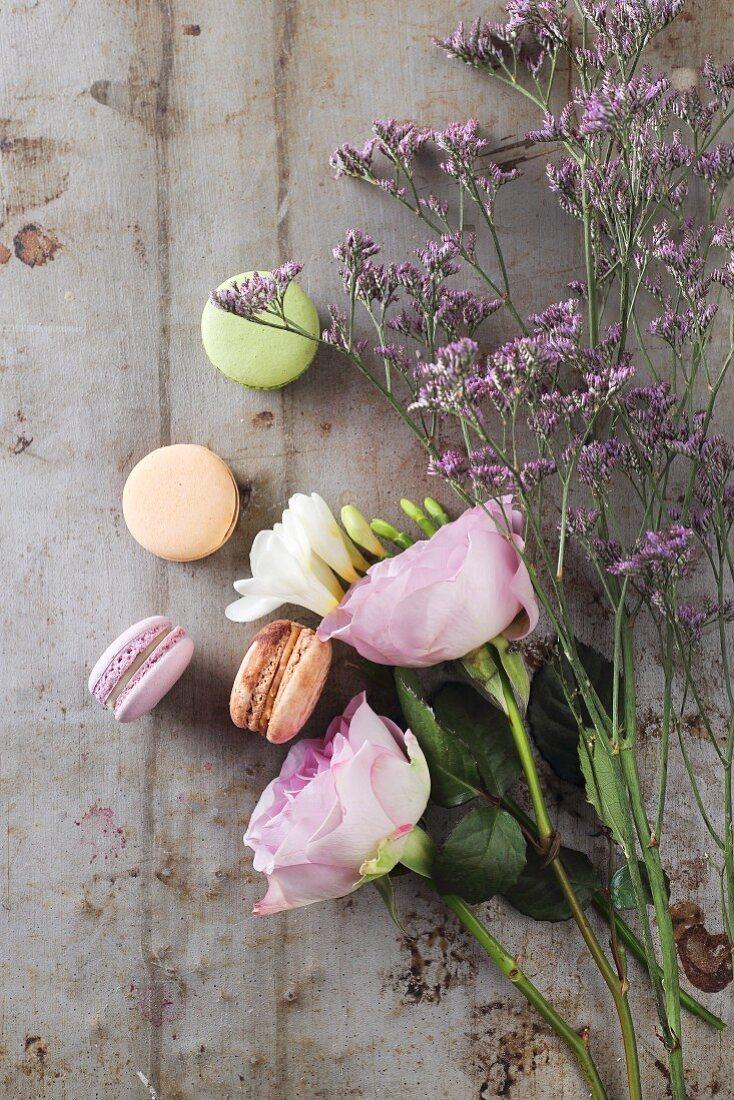 Various macarons beside violet flowers