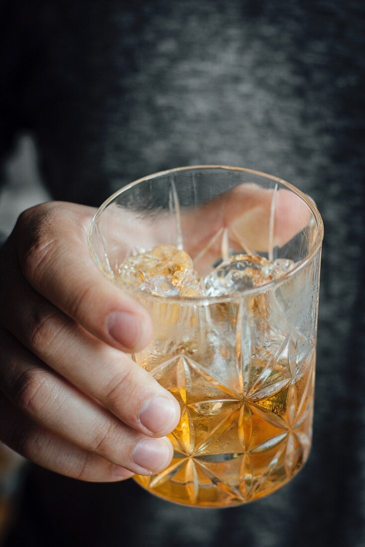 A hand holding a glass with an old fashioned cocktail