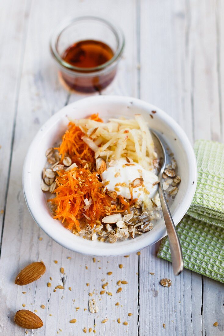 Fresh muesli with cereal flakes, apple, carrots and maple syrup