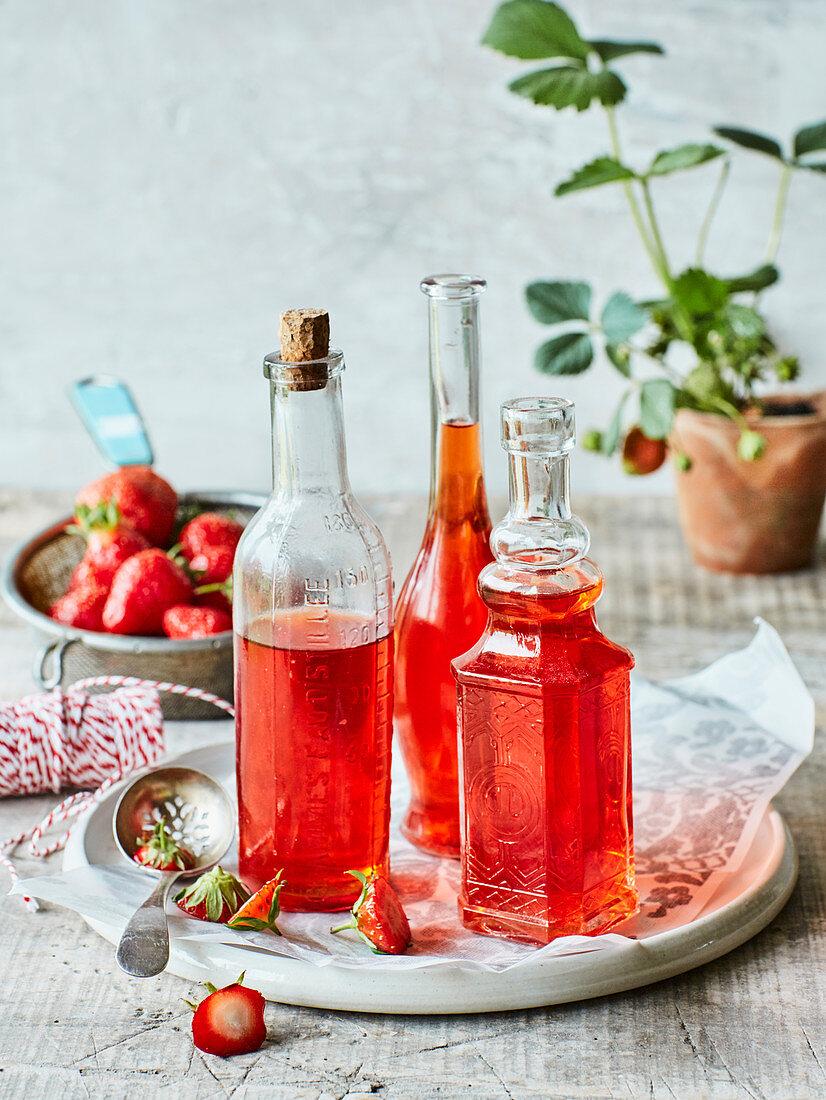 Homemade strawberry vinegar in decorative glass bottles