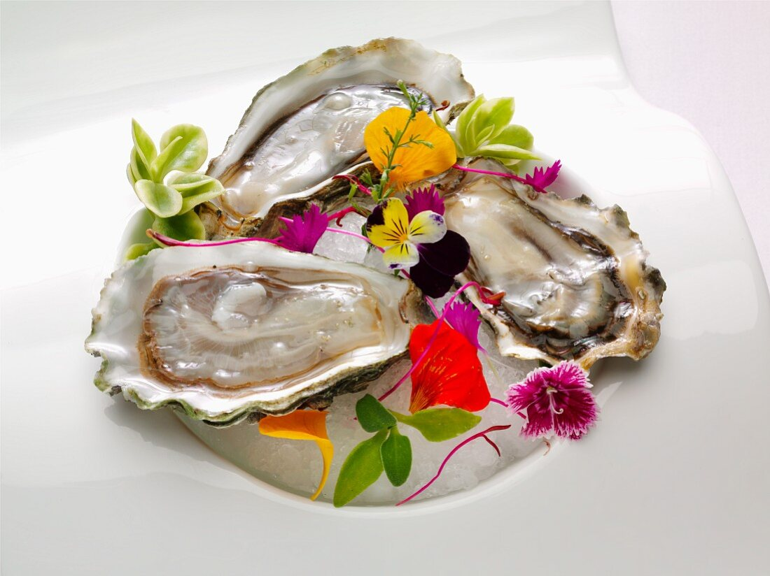 A plate of three oysters on half shell garnished with edible flowers
