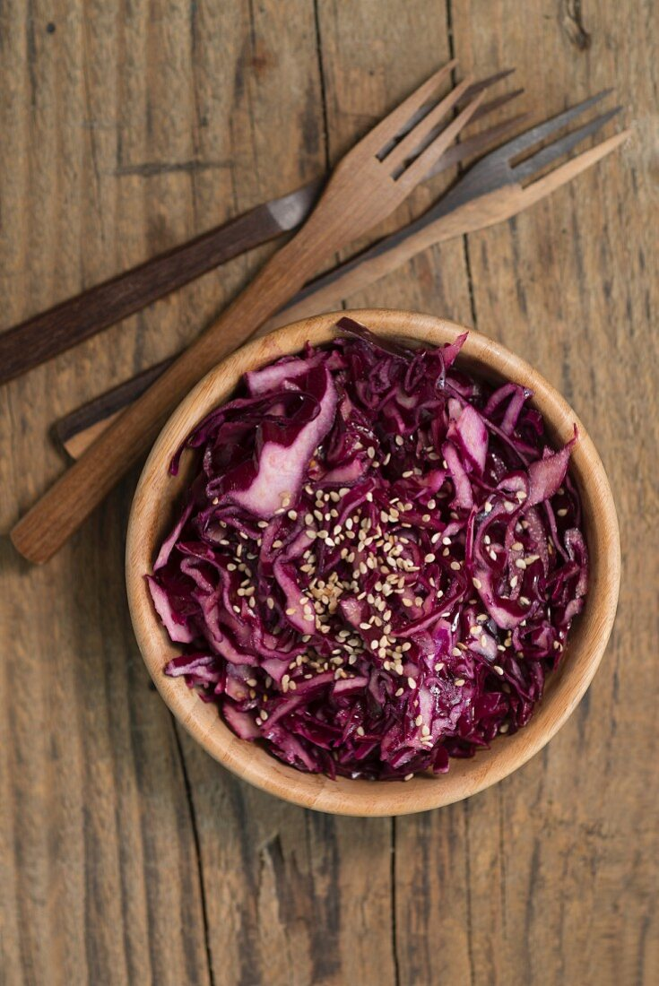 Red cabbage salad with sesame seeds in a wooden bowl (top view)