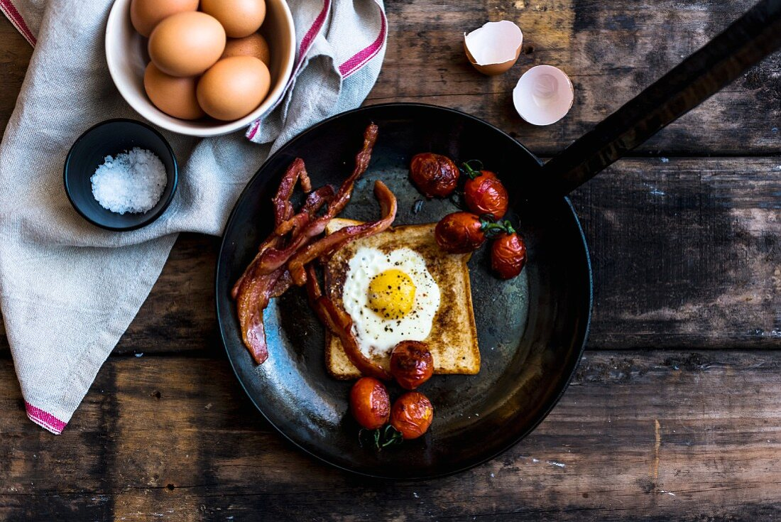 Toast with a fried egg, bacon, and tomatoes in a pan (top view)