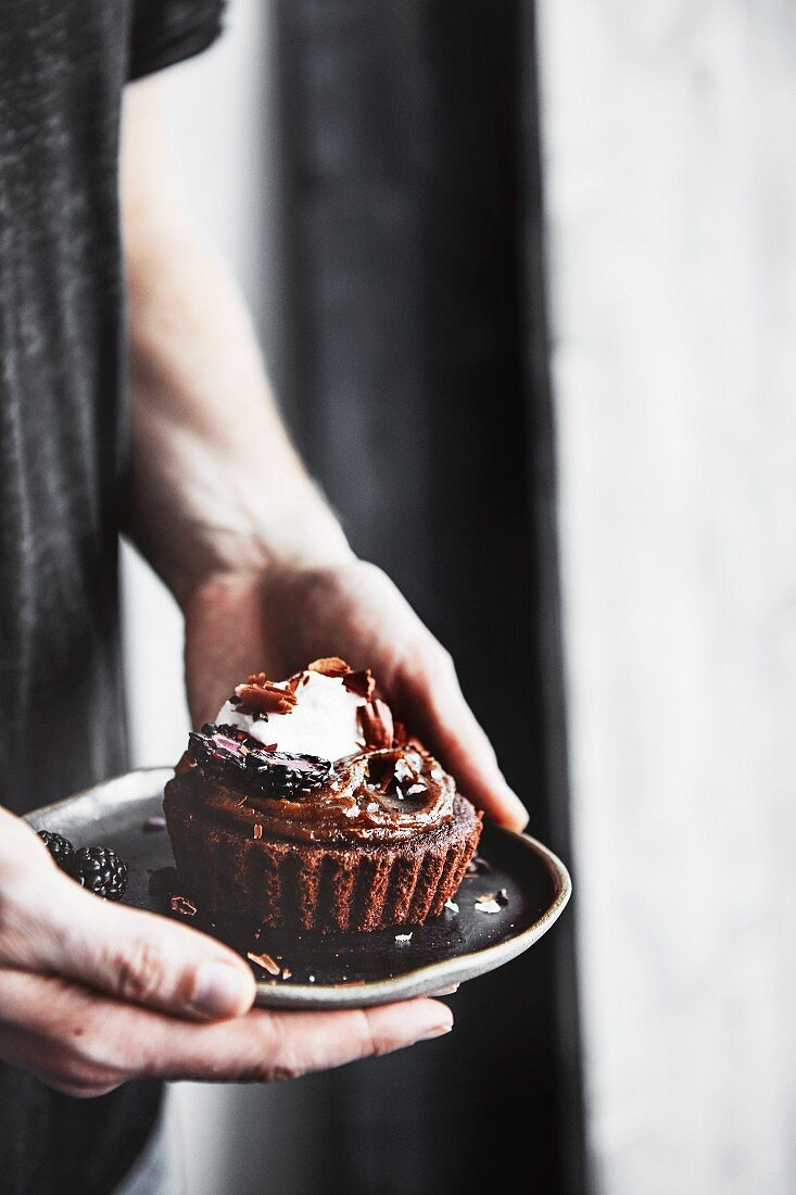 A person holding a plate of paleo chocolate tarts in their hands