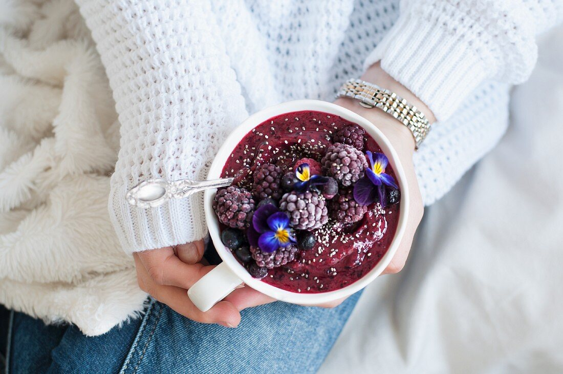 A smoothie bowl with blackberries, blueberries, mango, raspberries and edible flowers