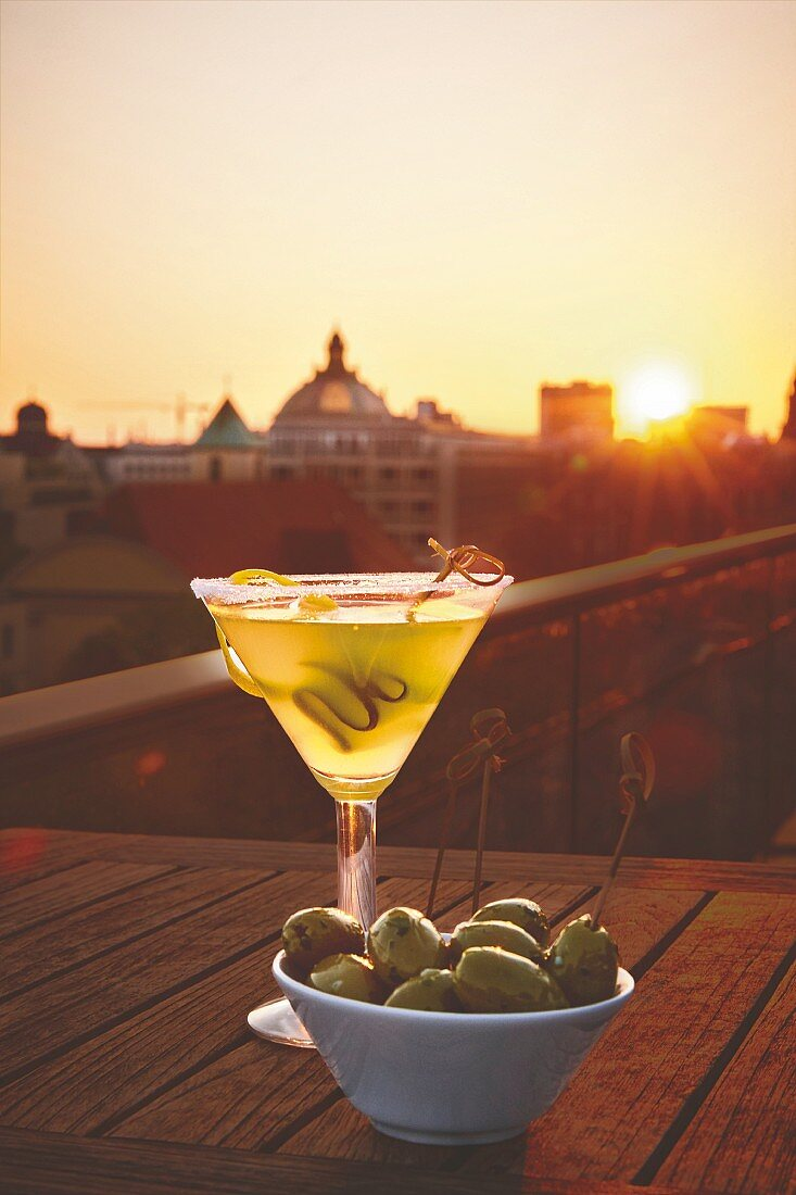 A glass of martini with olives at a rooftop bar as the sun sets