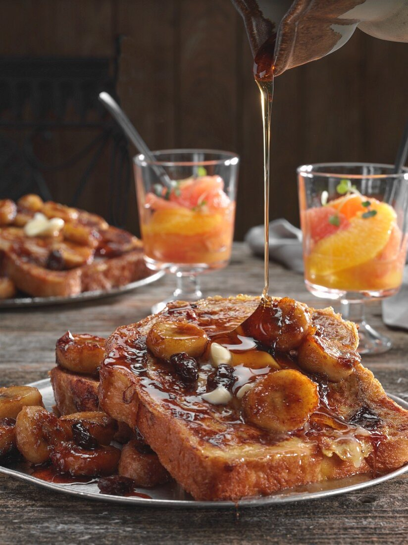 A plate of French Toast with sauteed bananas, butter and raisins drizzled with maple syrup on an old wooden table with fresh fruit cups in background