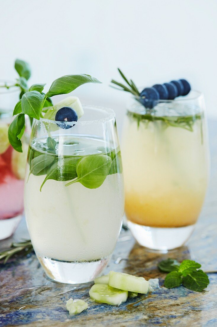 Cocktails with cucumber, basil, rosemary and blueberries