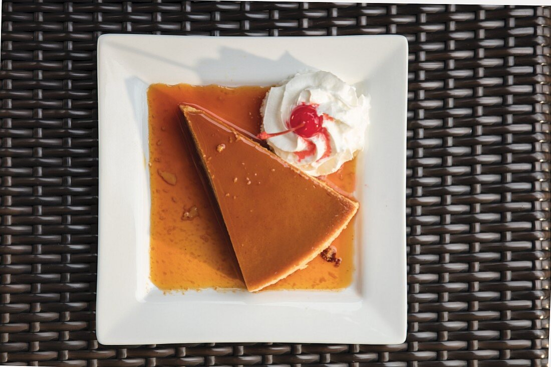 A triangle piece of flan with whipped cream and a cherry