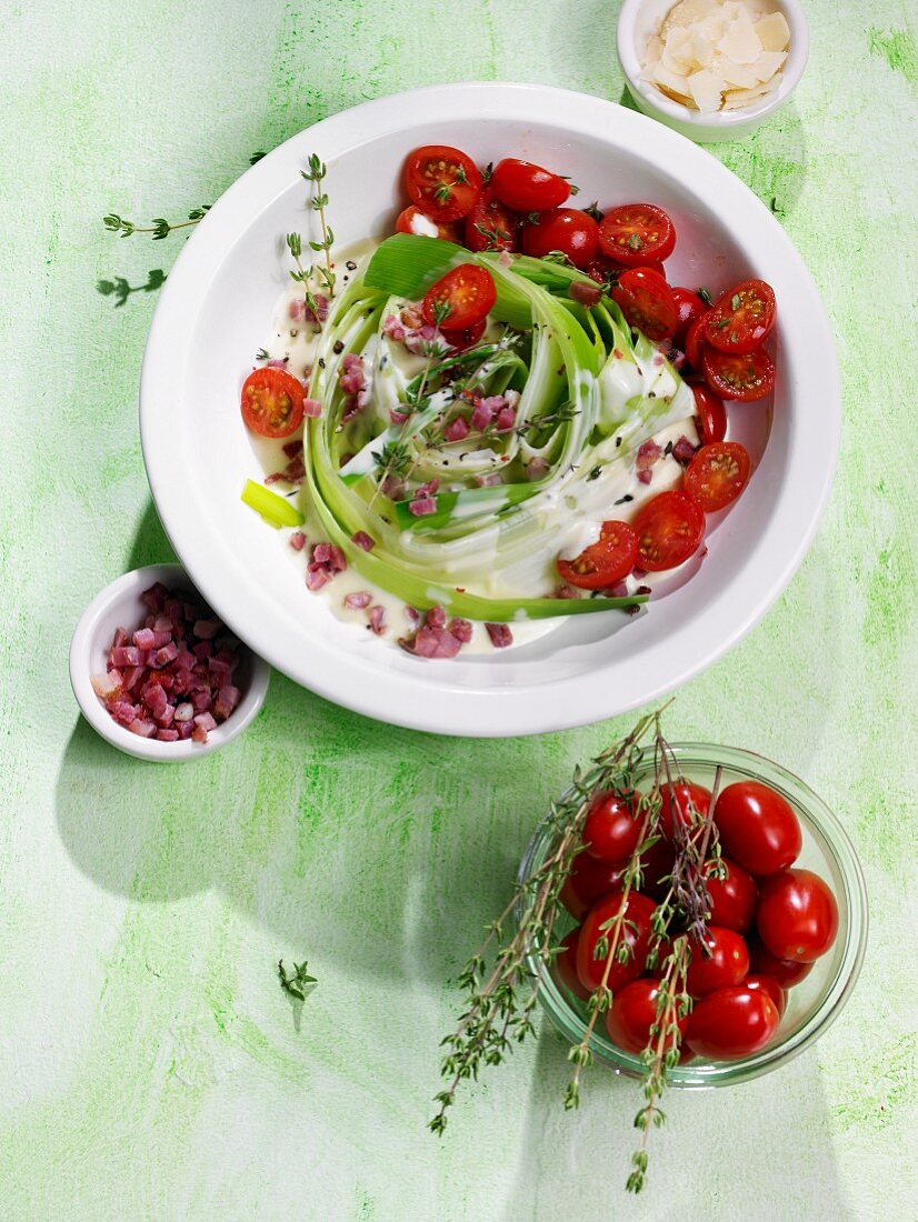 A leek nest with diced bacon, plum tomatoes and thyme