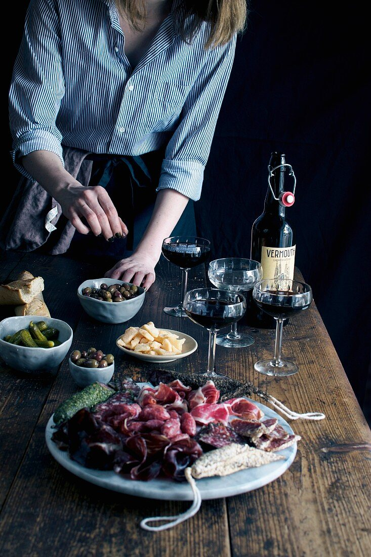 Various tapas served with vermouth on a rustic wooden table