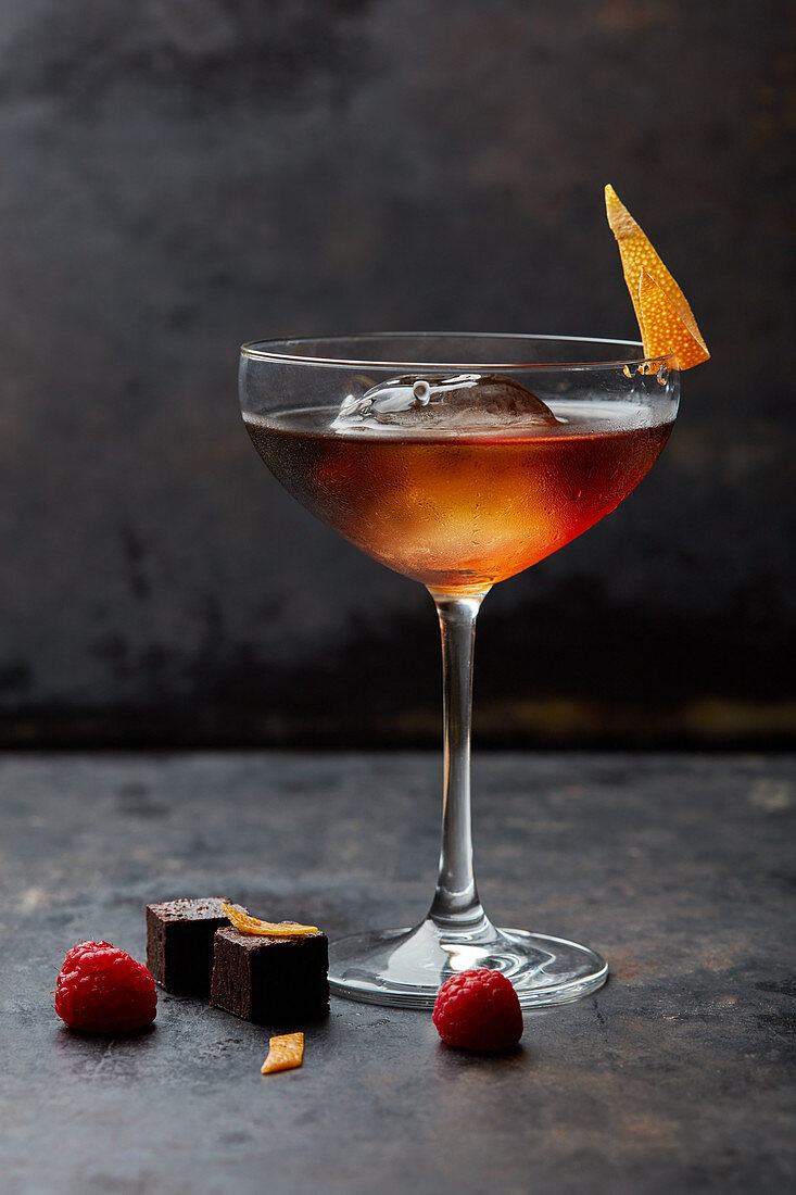 A cocktail with an ice cube and dried orange peel