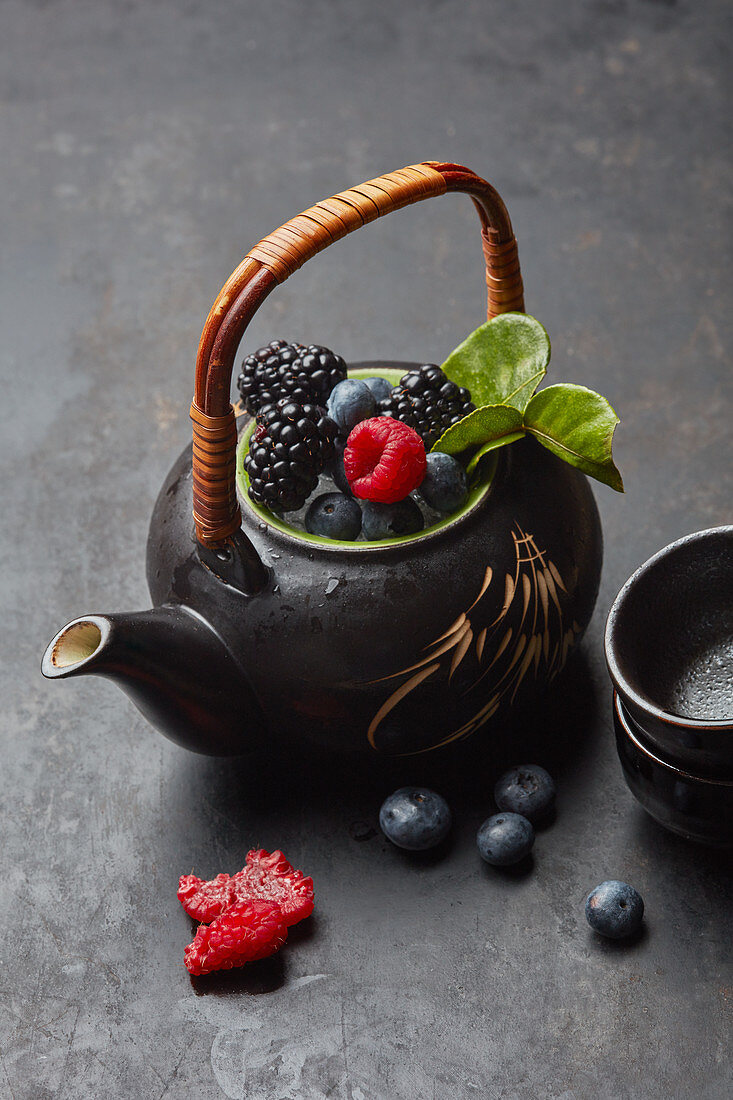 A teapot with fresh berries and tea leaves