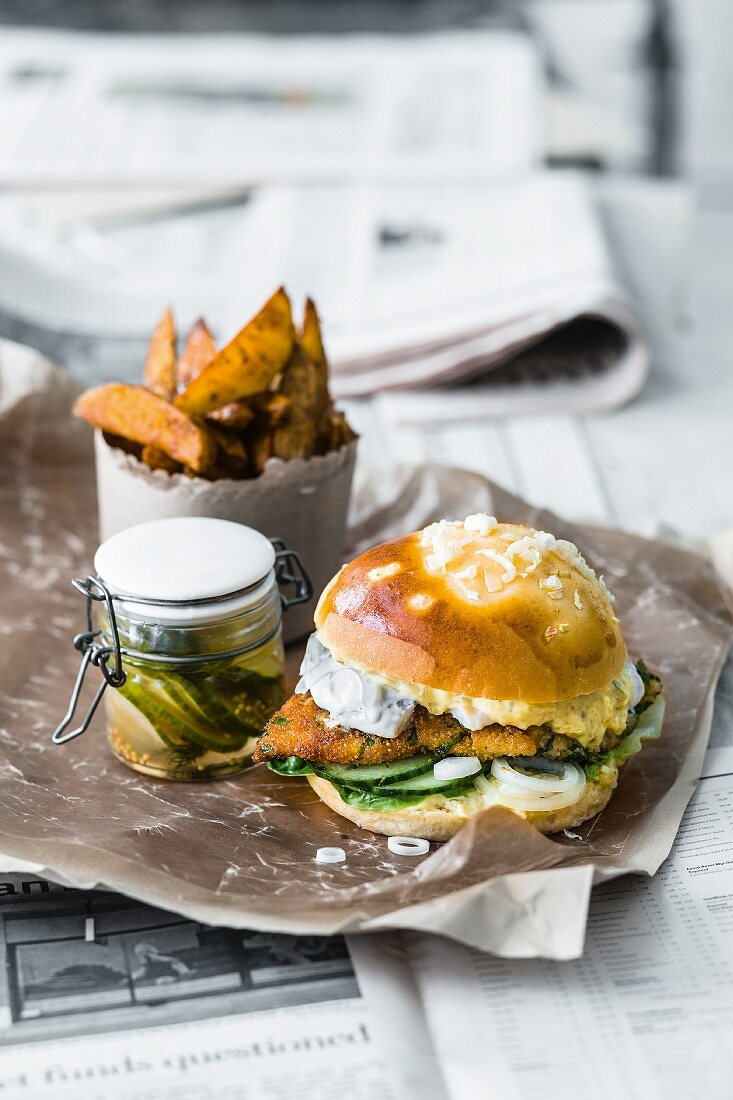 A fish burger with Danish remoulade, cucumber, herrings salad, and onions