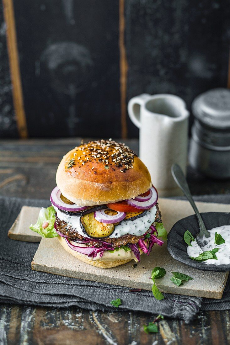 A lamb burger with hummus, mint yoghurt, and aubergine slices