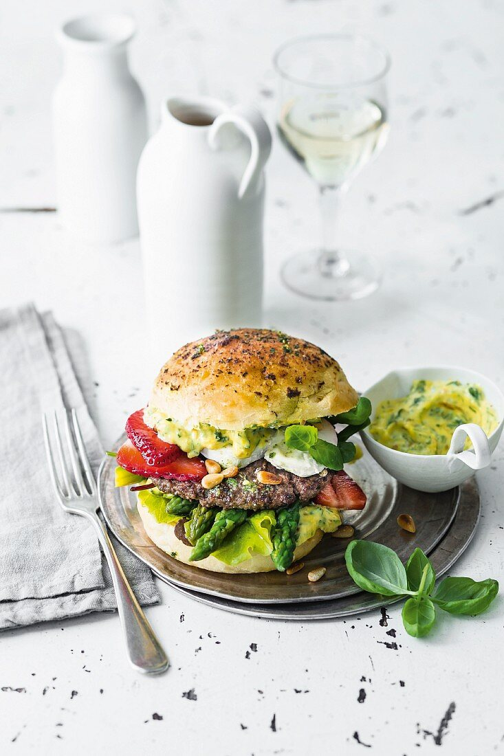 A burger with beef, goat's cheese, strawberries, and asparagus