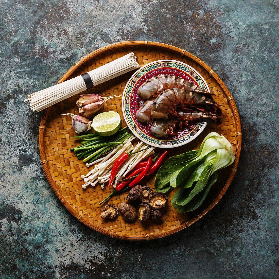 Ingredients for cooking Asian food with Tiger shrimps, udon noodles, mushrooms, greens, vegetables, spices on bamboo tray