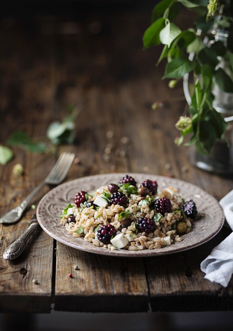 Cereal salad with spelt, olives, cheese, blackberries, basil on wooden table