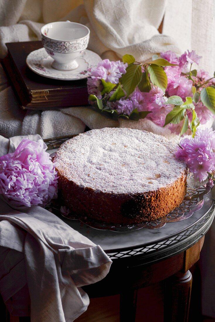 Chiffon Cake auf nostagischem Tisch umgeben von rosa Pfingst- und Kirschblüten