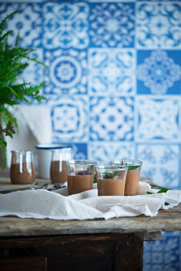 Mousse au Chocolate in Gläsern auf Holztisch vor blau-weiss gefliesster Wand