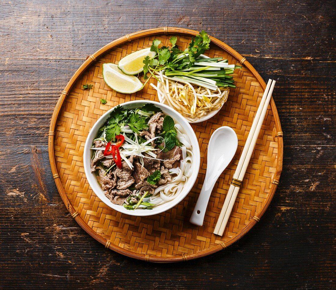 Pho Bo (Suppe mit Rindfleisch und Reisnudeln, Vietnam) auf Bambustablett