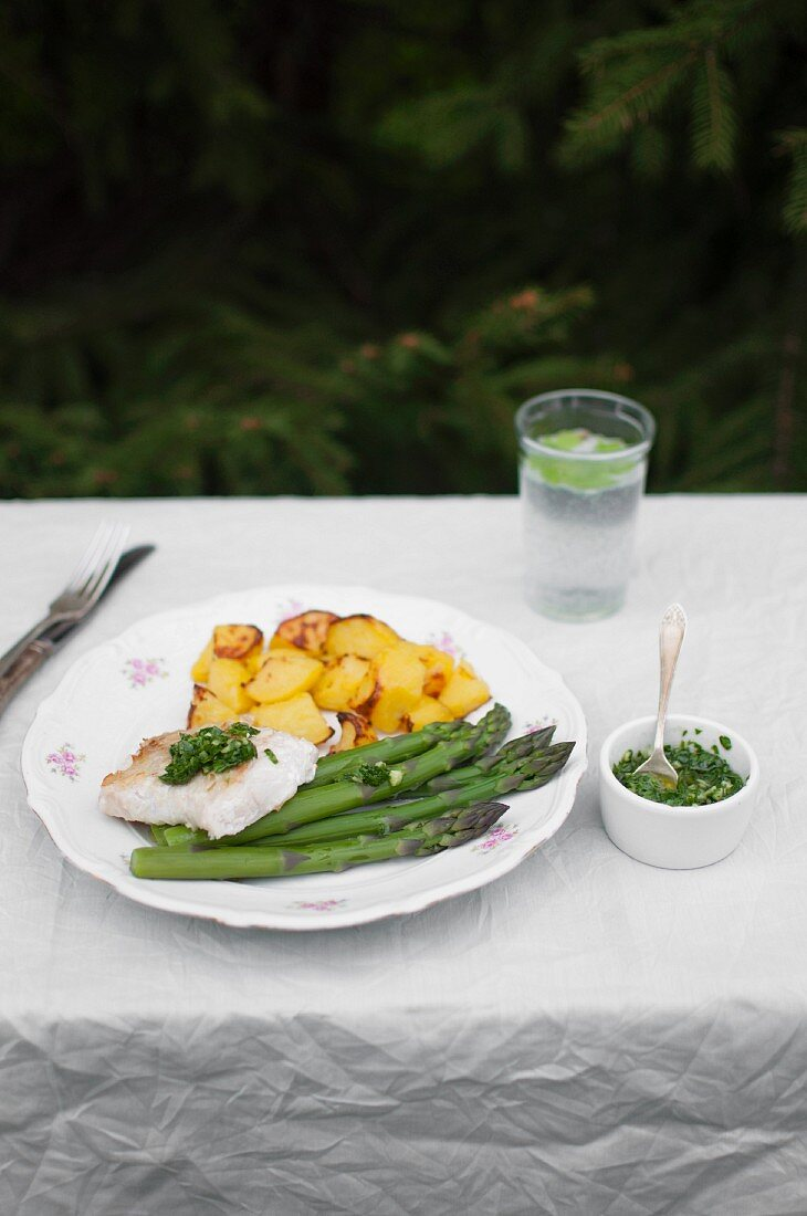 Fried cod served with roasted potatoes, green asparagus and herbal sauce (parsley, basil, garlic and olive oil)