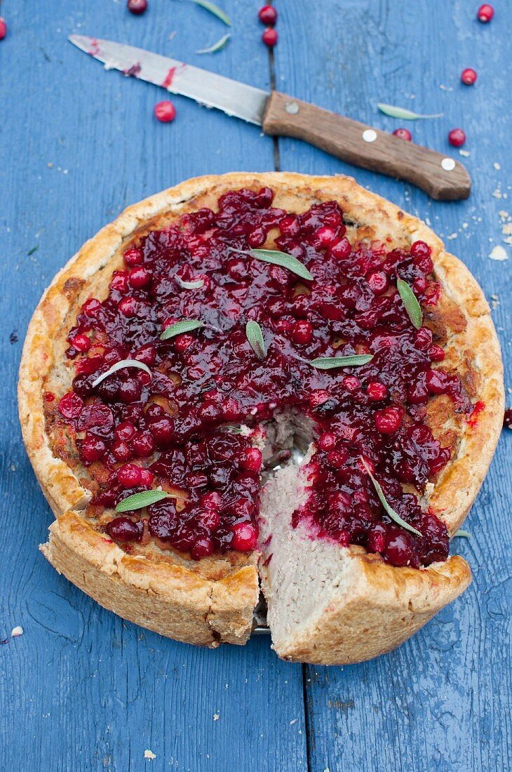 Christmas turkey shortcrust pie topped with cranberries and sage