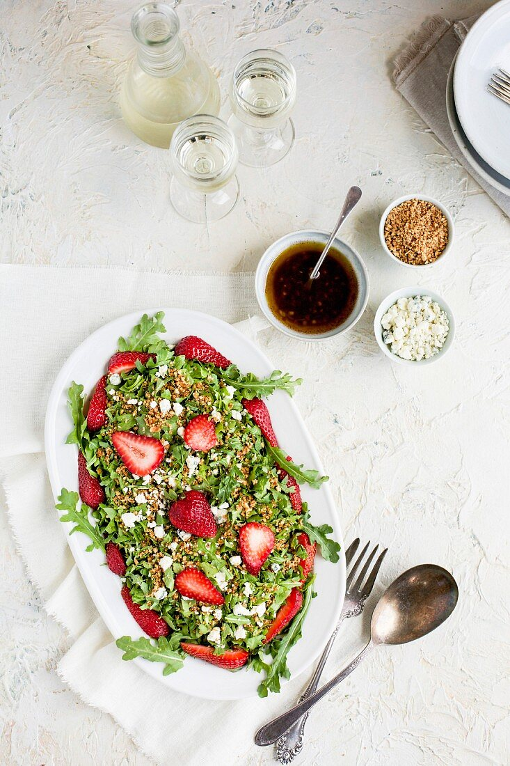 Strawberry Arugula Salad with Hibiscus Vinaigrette served with white wine on a white plaster background