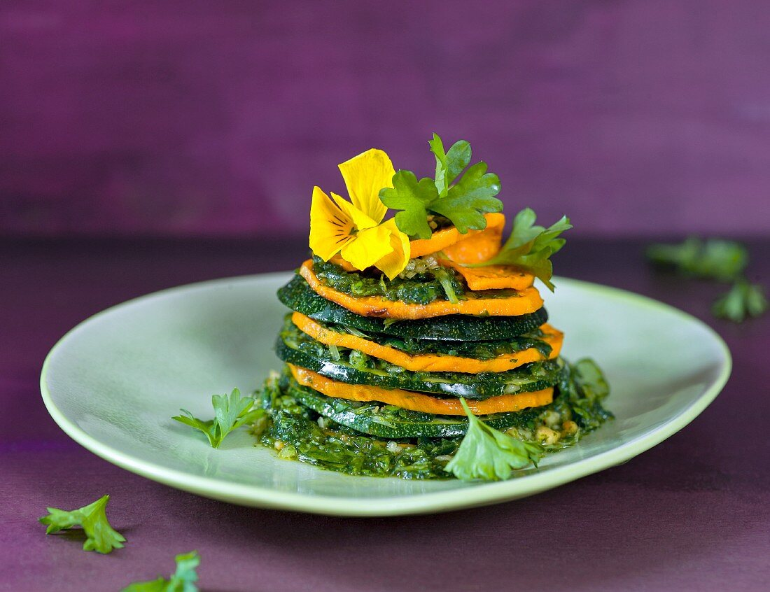 A zucchini and sweet potato tower with parsley