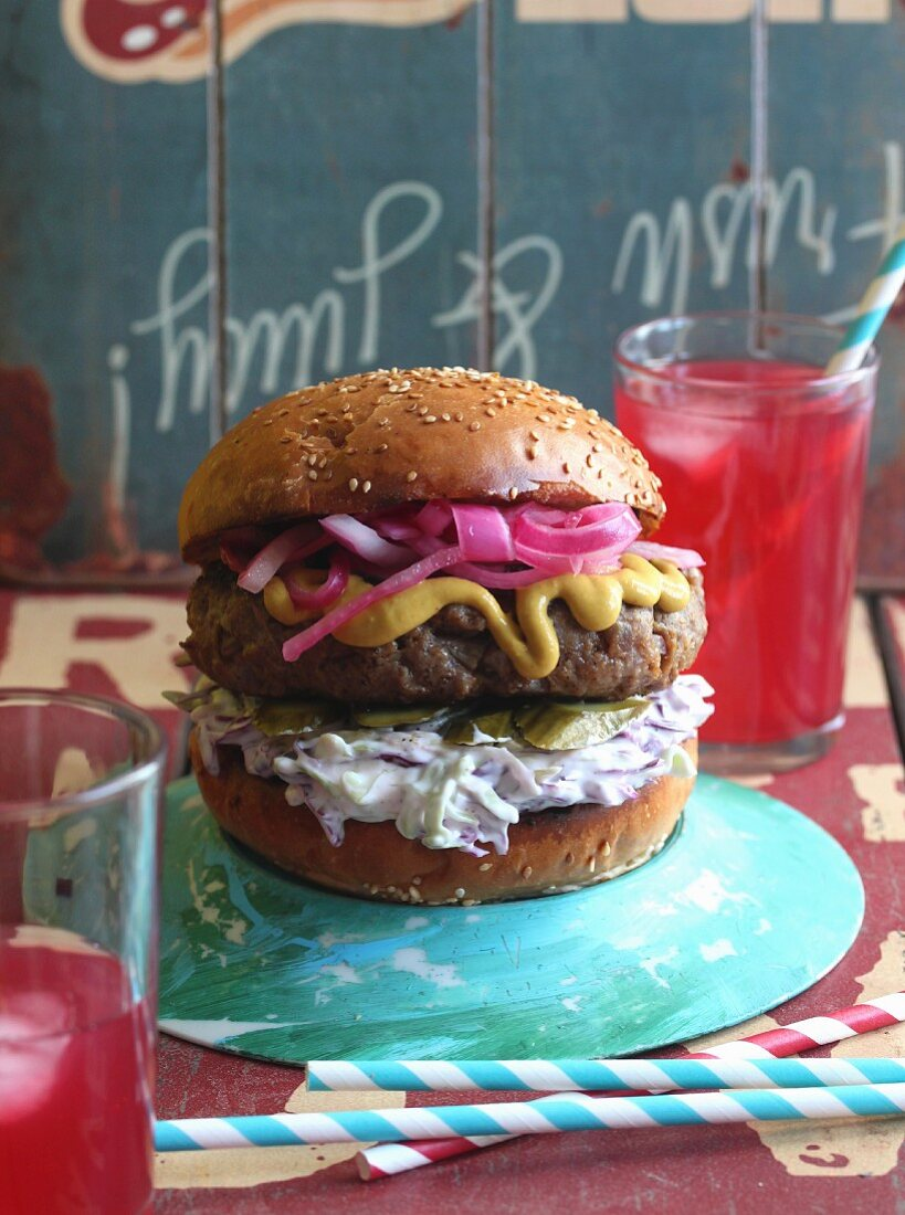 A burger with mustard and red onions