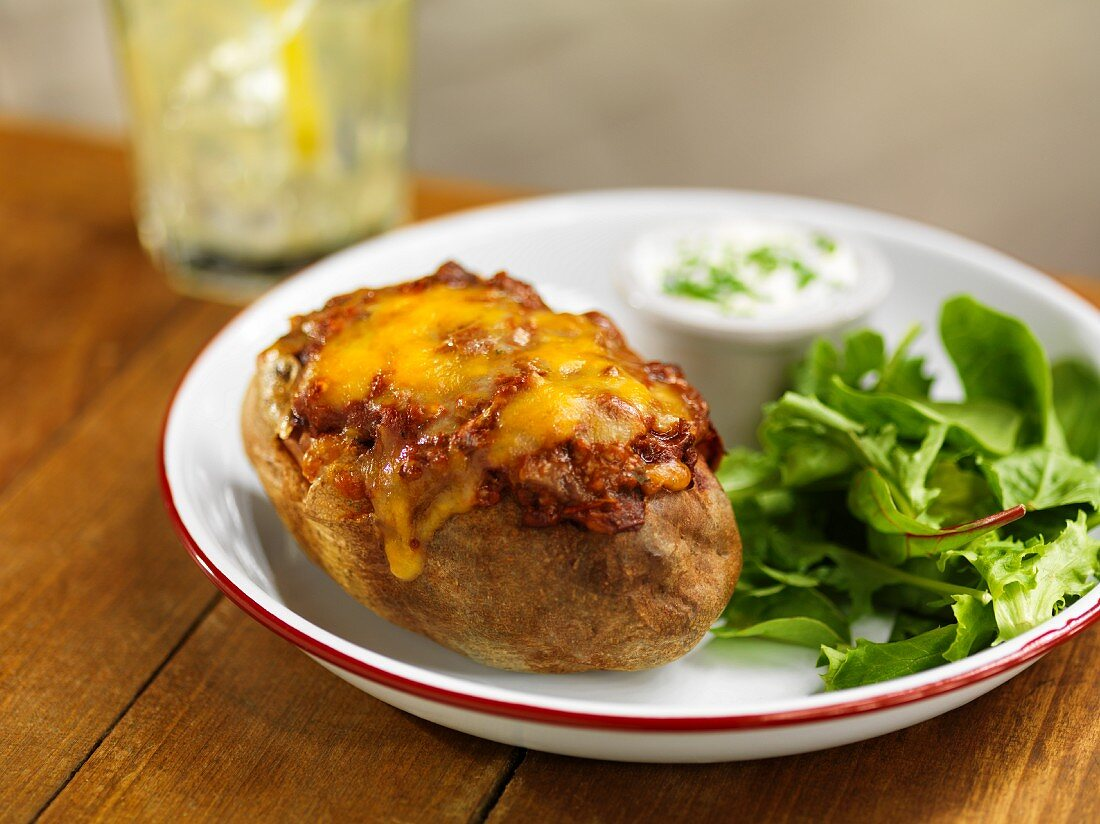 A baked potato with chili and lettuce