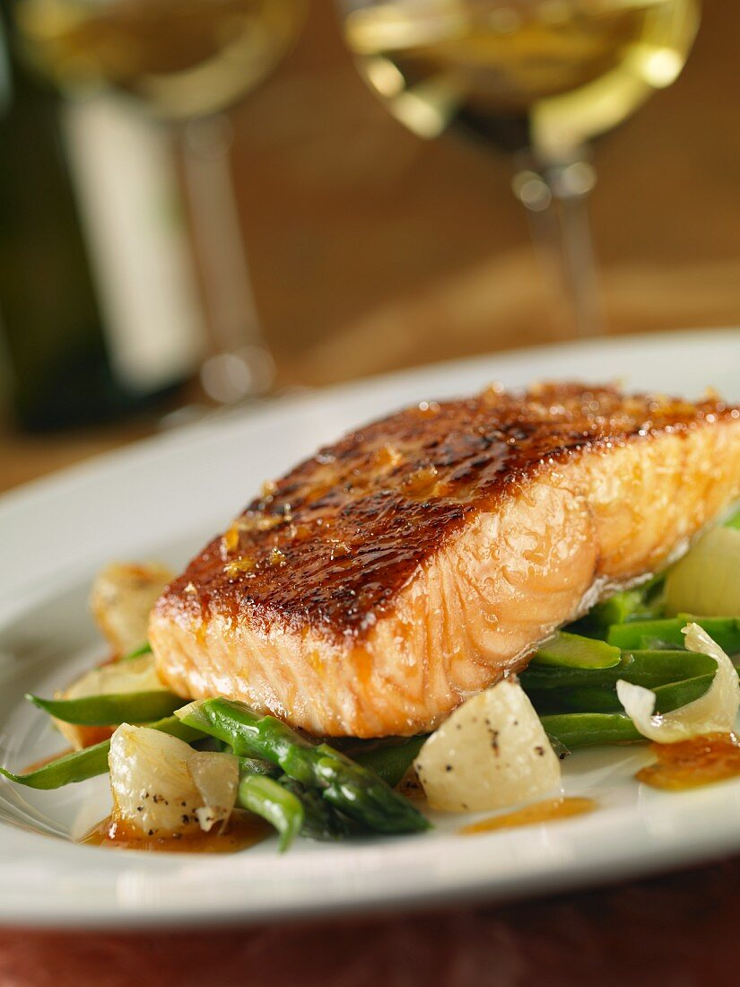 A salmon fillet in lemon sauce with spring vegetables
