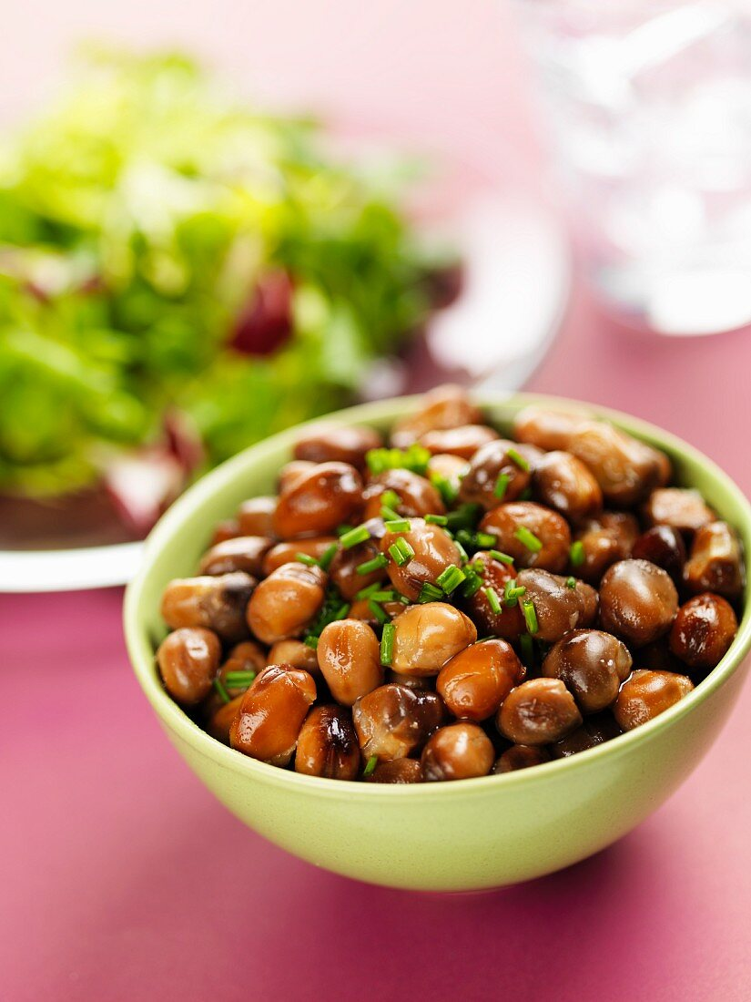 Brown beans with chives in a small bowl