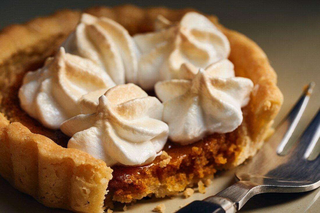 A mini pumpkin pie topped with meringue