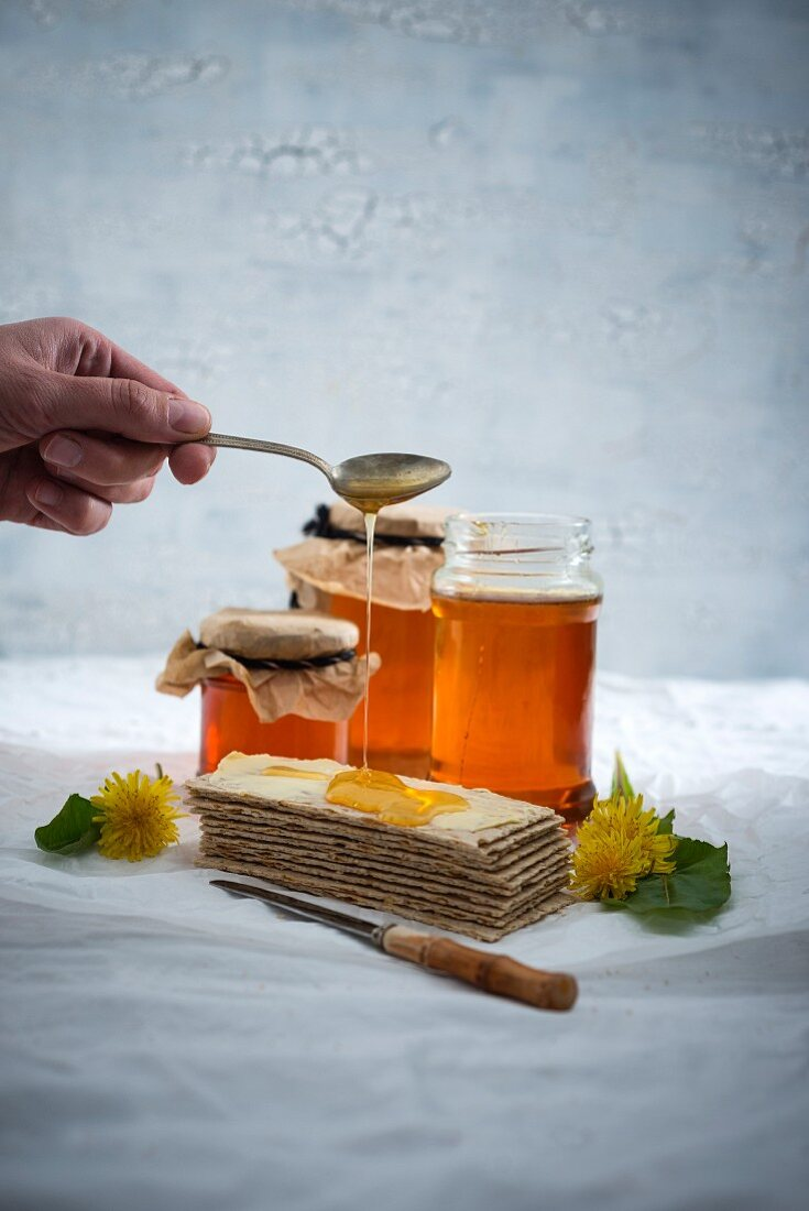 A woman's hand drizzling dandelion syrup on crispbreads
