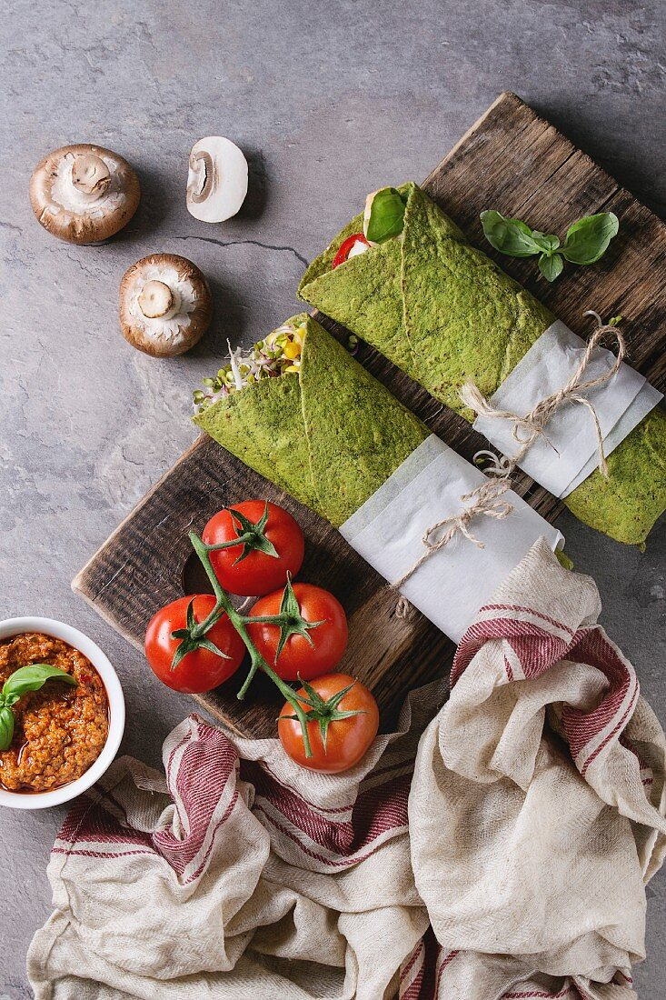 Green spinach matcha tortillas wrapped in paper with ingredients above