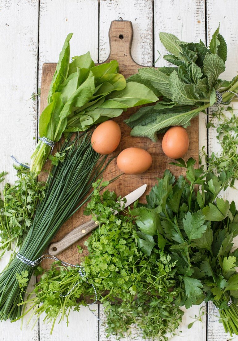 Ingredients for making green sauce on a chopping board with a knife
