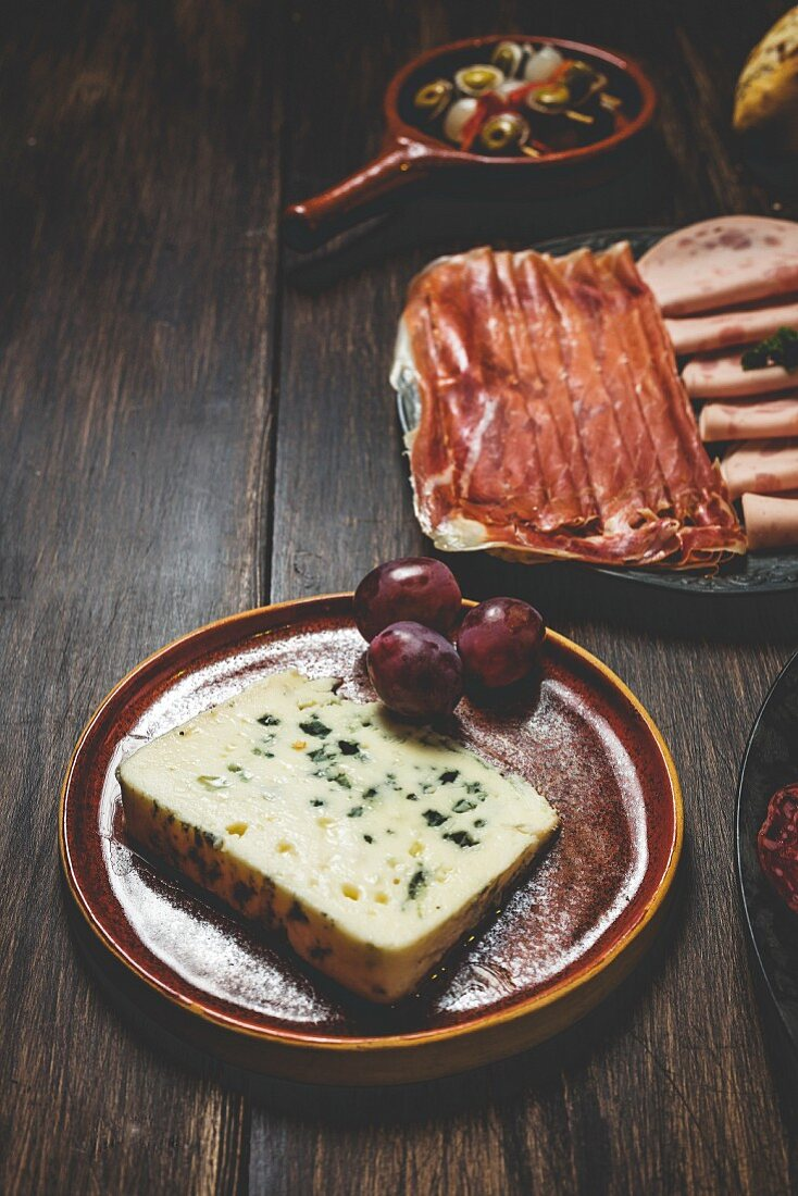 Cheese, ham, and salami on plates (Spain)