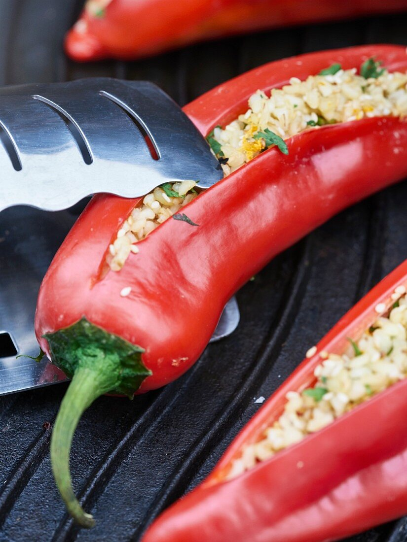 Red peppers stuffed with bulgur wheat and herbs on a grill