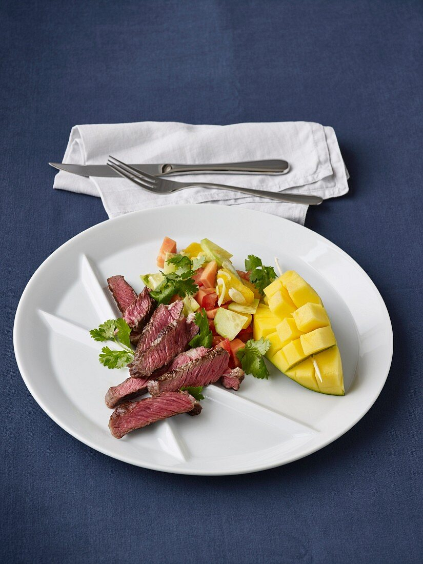 Grilled entrecote with a salad of papaya, mango, cucumber, tomatoes and coriander green