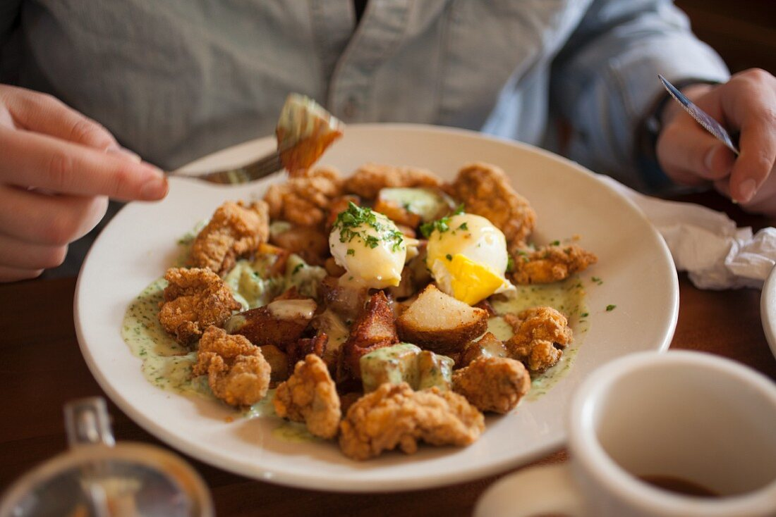 Poached eggs over roasted home fries with creamed spinach and crispy fried oysters